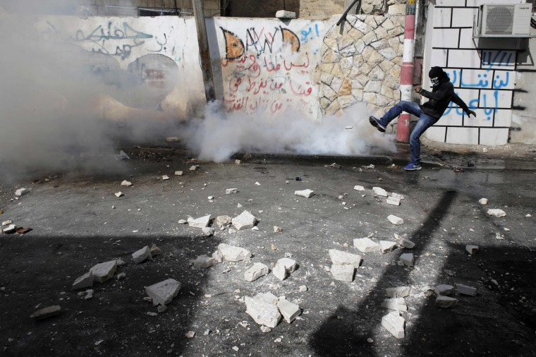 A Palestinian kicks back a tear gas canister fired by Israeli security forces during clashes in the Abu Tor neighbourhood of east Jerusalem October 30, 2014. Israeli police on Thursday shot dead Moataz Hejazi, a 32-year-old Palestinian suspected of having tried hours earlier to kill Yehuda Glick, a far-right Jewish activist, leading to clashes in East Jerusalem and fears of a new Palestinian uprising. REUTERS/Ammar Awad