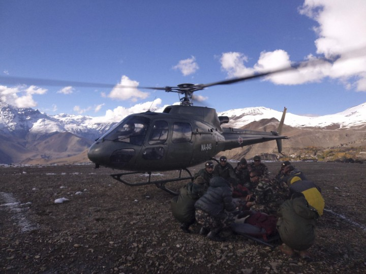 Nepalese army personnel surround a victim rescued from the avalanche as they wait for a helicopter to land at Thorang-La in Annapurna Region in this October 15, 2014 handout photo provided by Nepal Army. At least 12 people, including eight foreign hikers and a group of yak herders, were killed in Nepal by unseasonal blizzards and avalanches triggered by the tail of cyclone Hudhud, officials said on Wednesday. (REUTERS/Nepal Army)