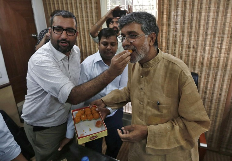 Indian children's right activist Kailash Satyarthi (R) is offered sweets by a well-wisher at his office in New Delhi October 10, 2014. Pakistani teenager Malala Yousafzai, who was shot in the head by the Taliban in 2012 for advocating girls' right to education, and Satyarthi won the 2014 Nobel Peace Prize on Friday. Satyarthi, 60, and Yousafzai were picked for their struggle against the oppression of children and young people, and for the right of all children to education, the Norwegian Nobel Committee said. (Adnan Abidi/Reuters)