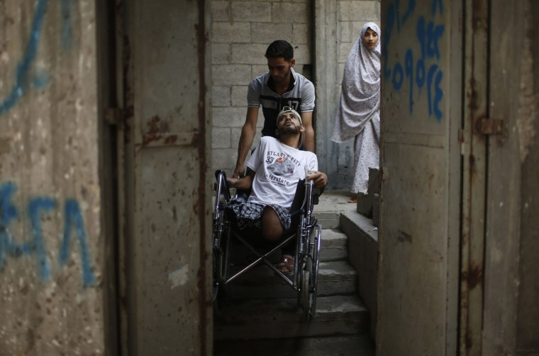 The brother of wheelchair-bound Palestinian Mohammed Abed al-Dayem, 25, pushes him as he enters his house in Beit Lahiya town in the northern Gaza Strip October 15, 2014. Medics say that Abed al-Dayem lost both of his legs when Israeli shelling hit the UN-run school where they took refuge during the most recent conflict between Israel and Hamas. His father was killed while his mother lost her right eye in the same incident. (REUTERS/Mohammed Salem)
