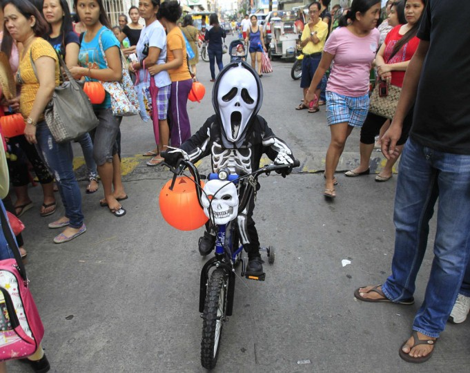 A school boy wearing a mask and a costume arrives on a bicycle before the start of a Halloween Parade along a street in Manila October 30, 2014. (Romeo Ranoco/Reuters)
