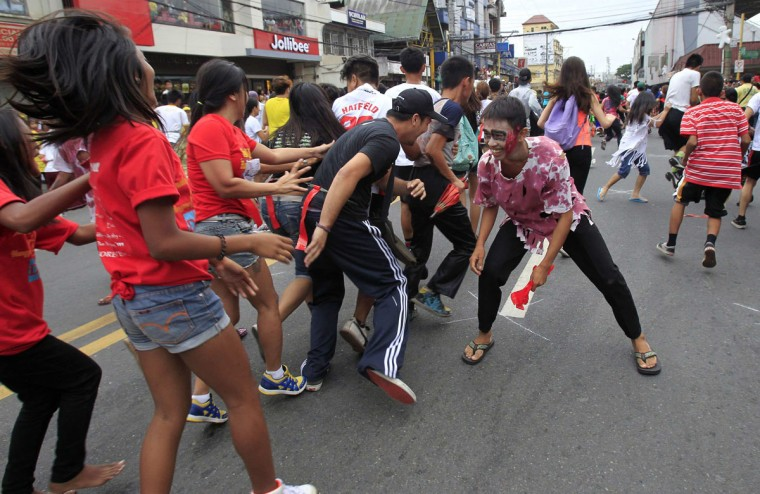 A man wearing a zombie costume chases participants during a Zombie Run held as part of Halloween celebrations in Marikina city, east of Manila October 30, 2014. (Romeo Ranoco/Reuters)