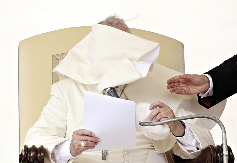 A gust of wind blows Pope Francis' mantle as he leads his weekly audience in Saint Peter's Square at the Vatican October 15, 2014. (REUTERS/Alessandro Bianchi)