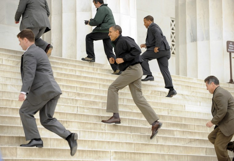 President Barack Obama sprints up the steps of the Lincoln Memorial surrounded by Secret Service agents, to visit with tourists, a day after Congress came to agreement on funding the federal government, emphasizing that national parks, monuments and museums are kept open and filled with visitors, in Washington April 9, 2011. (Mike Theiler/Reuters)