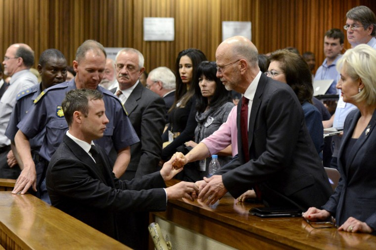 South African Olympic and Paralympic track star Oscar Pistorius (front L) holds the hands of family members after being sentenced at the North Gauteng High Court in Pretoria October 21, 2014. A South African judge on Tuesday sentenced Pistorius to five years in prison for the negligent killing of his girlfriend Reeva Steenkamp on Valentine's Day last year. (REUTERS/Herman Verwey/Pool)