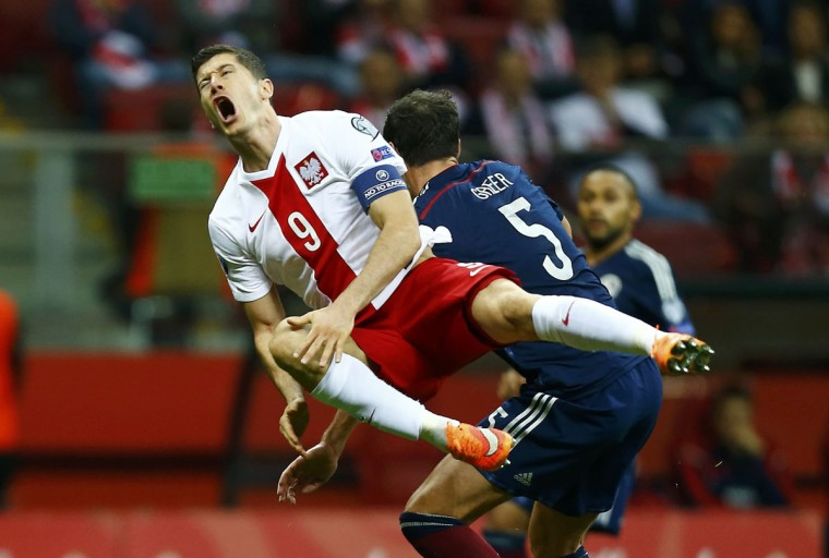 Robert Lewandowski (L) of Poland reacts after being fouled by Gordon Greer of Scotland during their Euro 2016 Group D qualifying soccer match at National Stadium in Warsaw October 14, 2014. (REUTERS/Kacper Pempel)