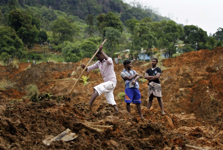 A man searches at the site of a landslide at the Koslanda tea plantation near Haldummulla October 30, 2014. Hopes of finding survivors under the mud and rubble of the landslide in south-central Sri Lanka had run out by first light on Thursday, though a government minister cut the estimated death toll to more than 100 from 300 the previous night. REUTERS/Dinuka Liyanawatte