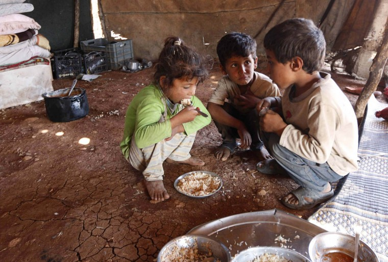Internally displaced children, who along with their family fled the violence in Aleppo's Handarat area, eat inside a tent in the northern countryside of Aleppo October 8, 2014. (Jalal Al-Mamo/Reuters photo)