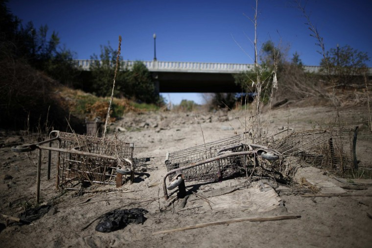 Discarded shopping carts lie in the dry Tule river bed in Porterville, California October 14, 2014. In one of the towns hardest hit by California's drought, the only way some residents can get water to flush the toilet is to drive to the fire station, hand-pump water into barrels and take it back home. The state's three-year drought comes into sharp focus in Tulare County, the dairy and citrus heart of the state's vast agricultural belt, where more than 500 wells have dried up. (Lucy Nicholson/Reuters)