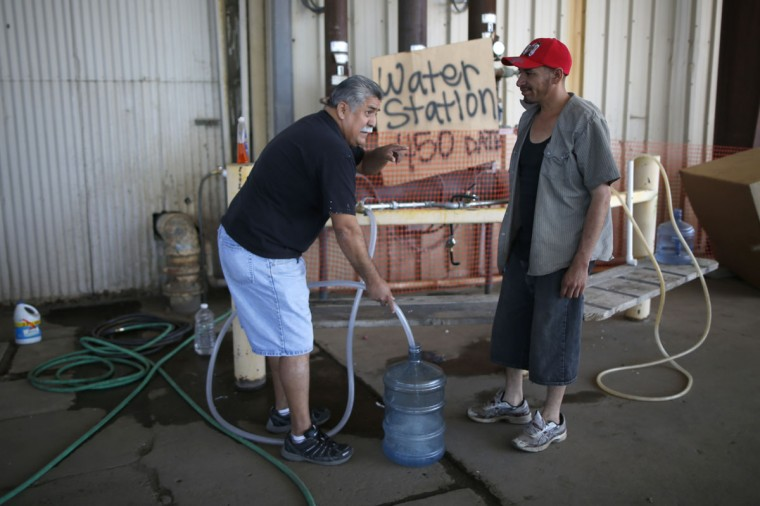 Pastor Frankie Olmedo, 56, (L) who volunteers four hours a day to hand out water, fills up a container for Luis Bocanegra, 35, in Porterville, California October 14, 2014. In one of the towns hardest hit by California's drought, the only way some residents can get water to flush the toilet is to drive to the fire station, hand-pump water into barrels and take it back home. The state's three-year drought comes into sharp focus in Tulare County, the dairy and citrus heart of the state's vast agricultural belt, where more than 500 wells have dried up. (Lucy Nicholson/Reuters)