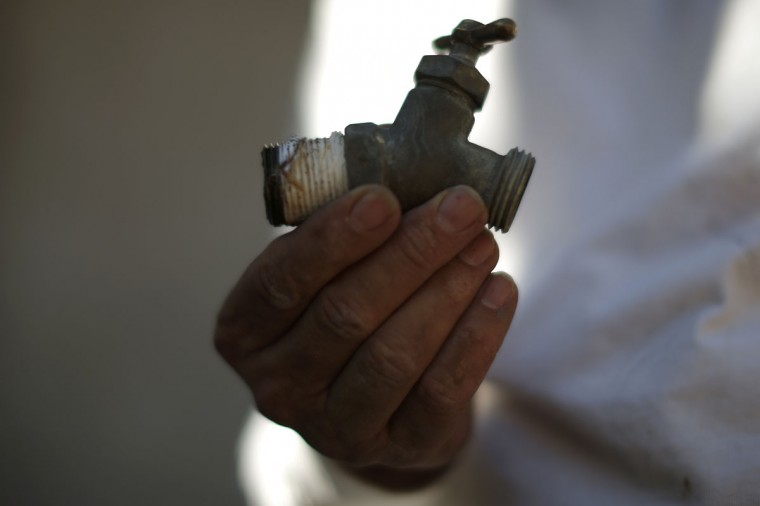 A workman holds the tap he removed from Manuel Rodriguez' home while installing a water pump in Porterville, California October 14, 2014. In one of the towns hardest hit by California's drought, the only way some residents can get water to flush the toilet is to drive to the fire station, hand-pump water into barrels and take it back home. The state's three-year drought comes into sharp focus in Tulare County, the dairy and citrus heart of the state's vast agricultural belt, where more than 500 wells have dried up. (Lucy Nicholson/Reuters)