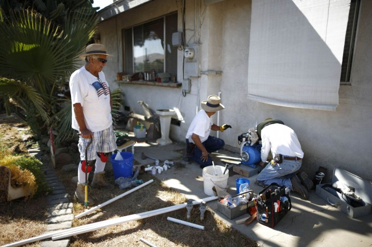 Manuel Rodriguez, 83, (L) watches as workmen install a water pump to carry water from an outdoor container into his home in Porterville, California October 14, 2014. In one of the towns hardest hit by California's drought, the only way some residents can get water to flush the toilet is to drive to the fire station, hand-pump water into barrels and take it back home. The state's three-year drought comes into sharp focus in Tulare County, the dairy and citrus heart of the state's vast agricultural belt, where more than 500 wells have dried up. (Lucy Nicholson/Reuters)