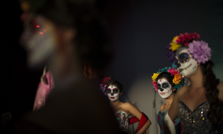 Models are pictured during a Quinceanera Magazine Catrina fashion show at a press reception ahead of the 15th annual Dia de los Muertos, or Day of the Dead, festival at Hollywood Forever Cemetery in Los Angeles, California October 24, 2014. The Day of the Dead festival has its origins in a pre-Hispanic Aztec belief that the dead return to Earth one day each year to visit their loved ones. The festival will be held on November 1. (Mario Anzuoni/Reuters)