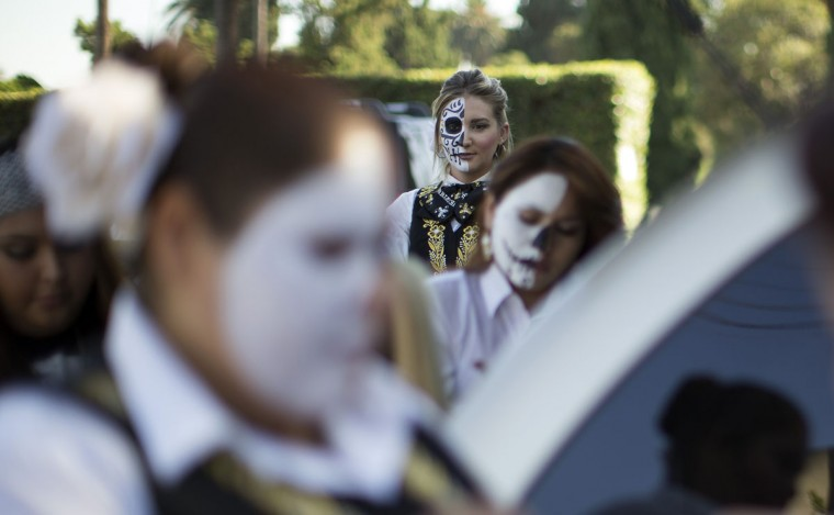 Mariachi Divas de Cindy Shea member Sabrina Rogers waits before a performance at a press reception ahead of the 15th annual Dia de los Muertos, or Day of the Dead, festival at Hollywood Forever Cemetery in Los Angeles, California October 24, 2014. The Day of the Dead festival has its origins in a pre-Hispanic Aztec belief that the dead return to Earth one day each year to visit their loved ones. The festival will be held on November 1. (Mario Anzuoni/Reuters)