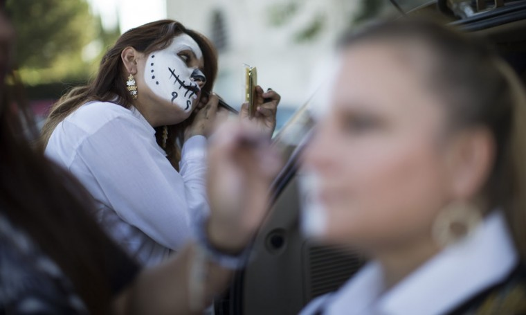 Mariachi Divas de Cindy Shea member Wendy Franco applies make-up before a performance at a press reception ahead of the 15th annual Dia de los Muertos, or Day of the Dead, festival at Hollywood Forever Cemetery in Los Angeles, California October 24, 2014. The Day of the Dead festival has its origins in a pre-Hispanic Aztec belief that the dead return to Earth one day each year to visit their loved ones. The festival will be held on November 1. (Mario Anzuoni/Reuters)