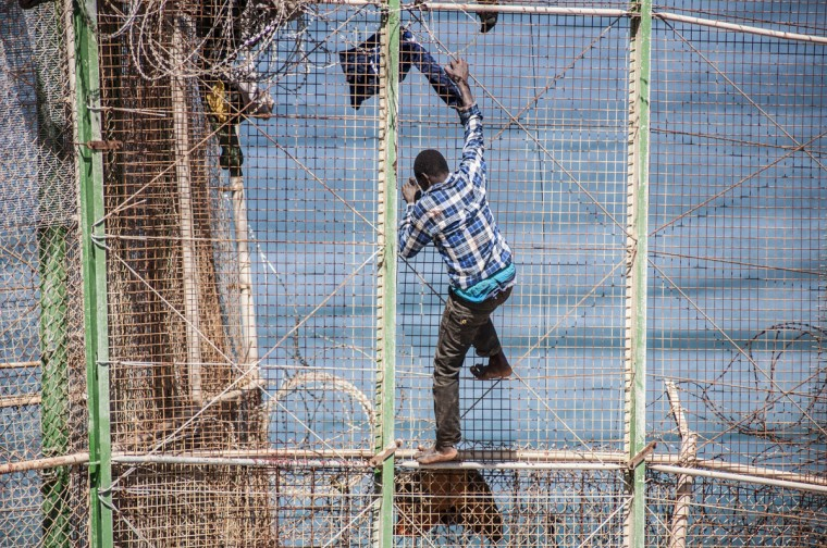An African migrant scales a border fence between Morocco and Spain's north African enclave of Melilla during their latest attempt to cross into Spanish territory on April 3, 2014. (REUTERS/Jesus Blasco de Avellaneda)