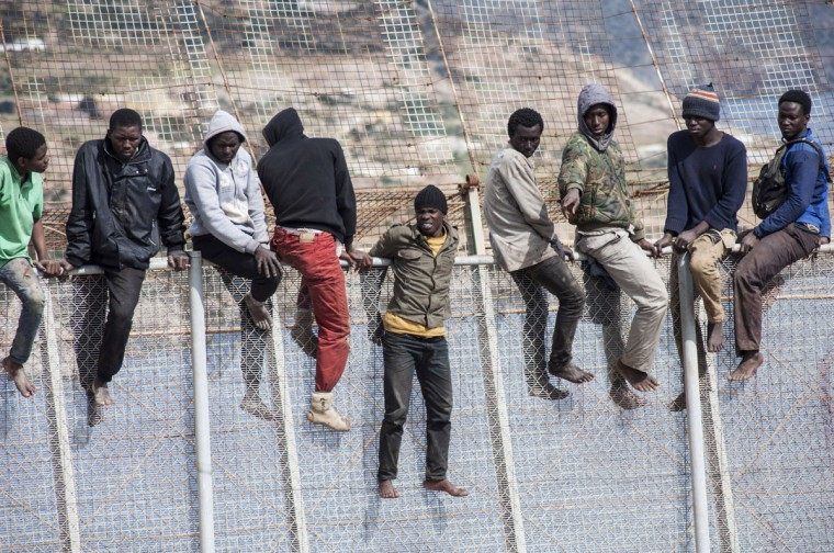 African migrants sit on top of a border fence between Morocco and Spain's north African enclave of Melilla during their latest attempt to cross into Spanish territory on April 3, 2014. (REUTERS/Jesus Blasco de Avellaneda)