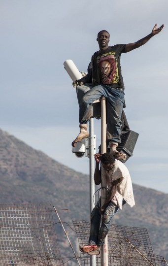 African migrants sit on top of a border fence covered in razor wire between Morocco and Spain's north African enclave of Melilla during their latest attempt to cross into Spanish territory on April 3, 2014. (REUTERS/Jesus Blasco de Avellaneda)