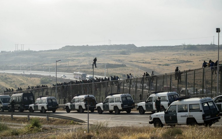 Vehicles from the Spanish Civil Guard are seen positioned at a border fence covered in razor wire as African migrants try to climb it during their latest attempt to cross into Spanish territory, between Morocco and Spain's north African enclave of Melilla on May 1, 2014. (REUTERS/Jesus Blasco de Avellaneda)