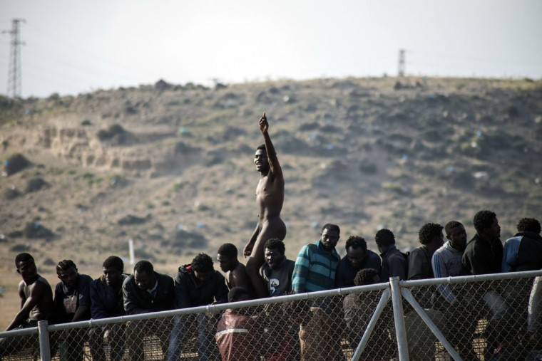 A naked African migrant stands on top of a border fence covered in razor wire during the migrants' latest attempt to cross into Spanish territory, between Morocco and Spain's north African enclave of Melilla, on May 1, 2014. (REUTERS/Jesus Blasco de Avellaneda)