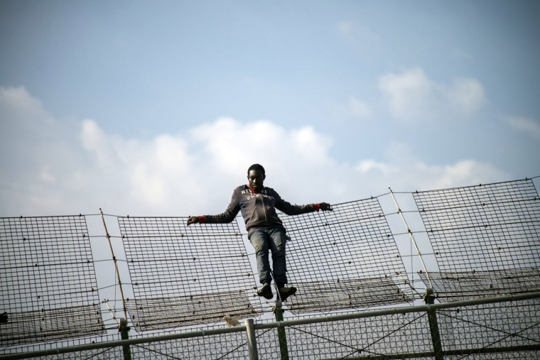 An African migrant rests on a border fence covered in razor wire during a latest attempt to cross into Spanish territory, between Morocco and Spain's north African enclave of Melilla on May 1, 2014. (REUTERS/Jesus Blasco de Avellaneda)