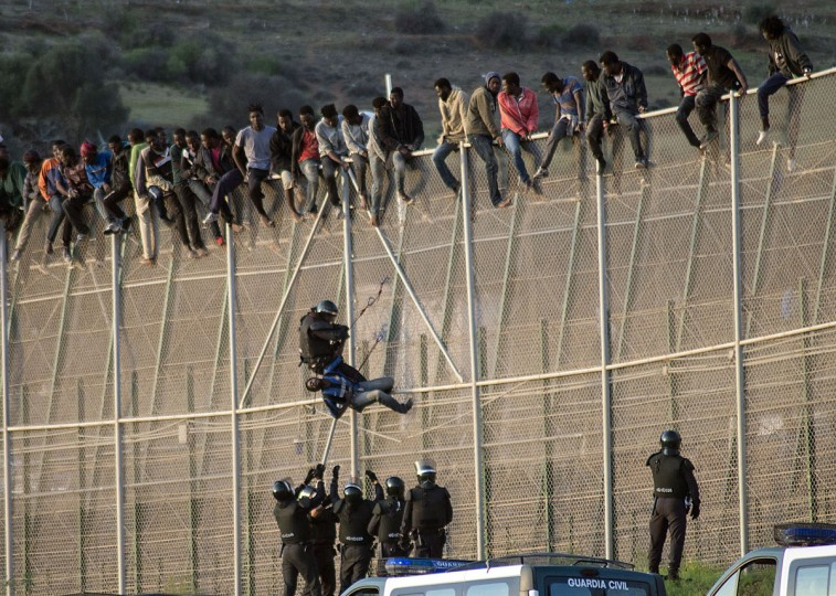 A Spanish Civil Guard pulls an African migrant from a border fence, as Spanish Civil Guard officers stand underneath, during an attempt to cross into Spanish territories, between Morocco and Spain's north African enclave of Melilla on October 15, 2014. (REUTERS/Jesus Blasco de Avellaneda)