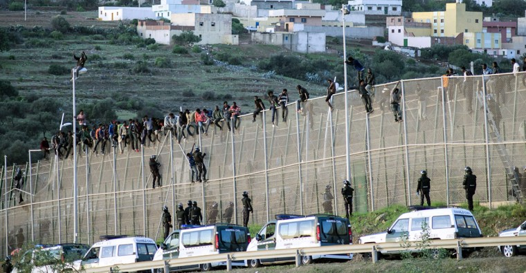 African migrants sit atop a border fence, as Spanish Civil Guard officers stand underneath, during an attempt to cross into Spanish territories, between Morocco and Spain's north African enclave of Melilla on October 15, 2014. (REUTERS/Jesus Blasco de Avellaneda)