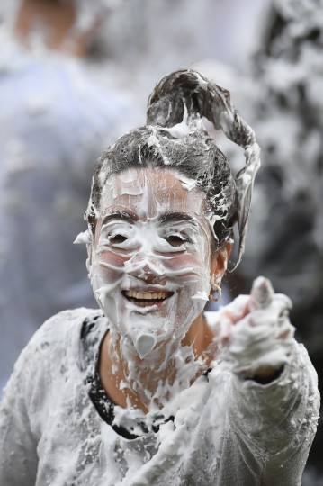 A student from St Andrew's University indulges in a tradition of covering oneself with foam to honor the 'academic family' on October 20, 2014, in St Andrews, Scotland. (Jeff J Mitchell/Getty Images)