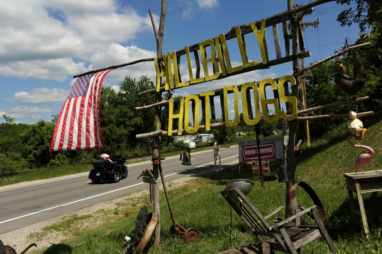 "A motorcycle rides past a roadside hotdog stand with a sign that reads ""Hillbilly Hotdogs"" in Lesage, West Virginia May 24, 2014. With coal production slowing due to stricter environmental controls, the availability of natural gas and a shift to surface mining, the state's coal country has been hit hard with job losses and business closures. (Robert Galbraith/Reuters)"