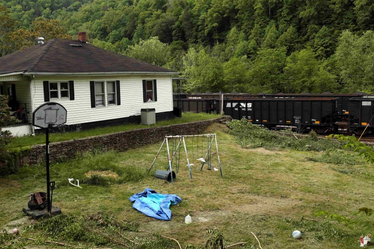 Coal trains sit idle in front of a home in Iaeger, West Virginia May 20, 2014. With coal production slowing due to stricter environmental controls, the availability of natural gas and a shift to surface mining, the state's coal country has been hit hard with job losses and business closures. (Robert Galbraith/Reuters)