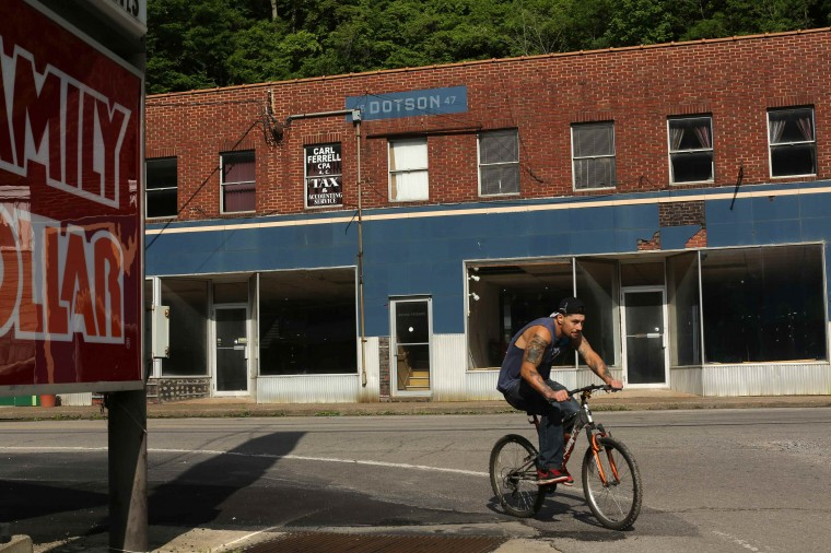 A man rides a bicycle past vacant store fronts in Gilbert, West Virginia May 22, 2014. With coal production slowing due to stricter environmental controls, the availability of natural gas and a shift to surface mining, the state's coal country has been hit hard with job losses and business closures. (Robert Galbraith/Reuters)