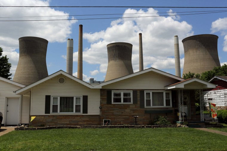 The John Amos coal-fired power plant is seen behind a home in Poca, West Virginia May 18, 2014. With coal production slowing due to stricter environmental controls, the availability of natural gas and a shift to surface mining, the state's coal country has been hit hard with job losses and business closures. (Robert Galbraith/Reuters)