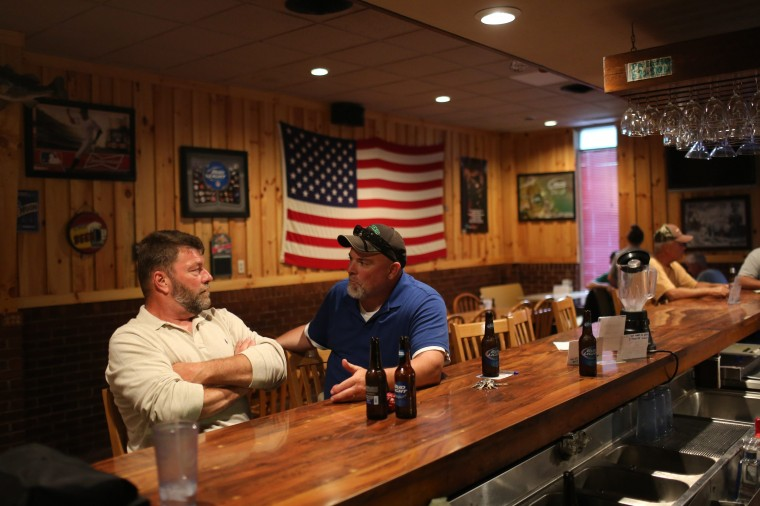 Unemployed coal miners Todd Hatfield (L) and Dave Houck talk at Hatfield's bar and restaurant in Gilbert, West Virginia May 22, 2014. (Robert Galbraith/Reuters)