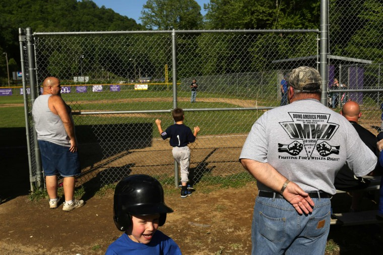 Retired coal miner Kenneth Douglas Sparks (R), watches his son coach his grandson's Little League baseball game in Gilbert, West Virginia May 19, 2014. Sparks, who said his father worked in the same coal mine for 47 years, worked in the mines himself for 20 years. (Robert Galbraith/Reuters)