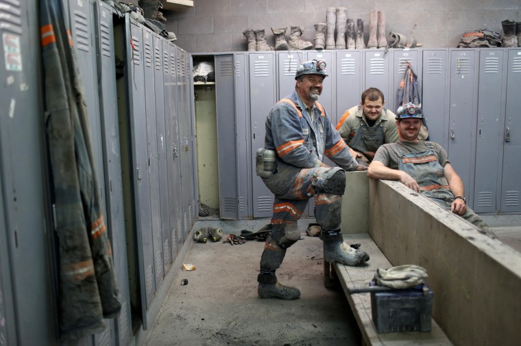 "Coal miners Rodney Blankenship (L), Roger Vanatter (C) and an unidentified colleague prepare for the start of their afternoon shift in the locker room of a coal mine near Gilbert, West Virginia May 22, 2014. Blankenship, 53, a coal miner for 30 years, said ""You go in there, hope to have good productivity on your shift, and get out safely."" (Robert Galbraith/Reuters)"