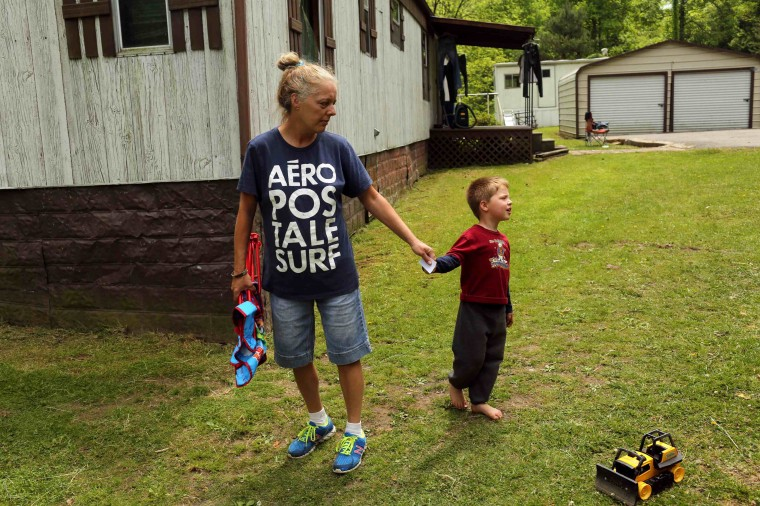 Sheila Ramsey holds the hand of her grandson, four-year-old Matthew Blankenship, in the home that they share with her father, and Matthew's father, near Gilbert, West Virginia May 20, 2014. Blankenship's father, Aaron, said he has been unable to find coal mining work for four years, and will probably have to leave the area. With coal production slowing due to stricter environmental controls, the availability of natural gas and a shift to surface mining, the state's coal country has been hit hard with job losses and business closures. (Robert Galbraith/Reuters)