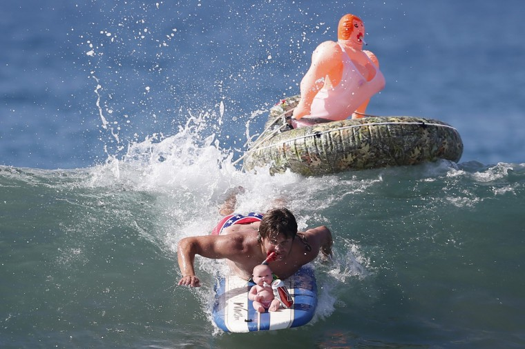John Broz, 28, rides a wave in a costume entitled 'The redneck yacht club' during the 7th annual ZJ Boarding House Haunted Heats Halloween surf contest in Santa Monica, California. (Lucy Nicholson/Reuters)
