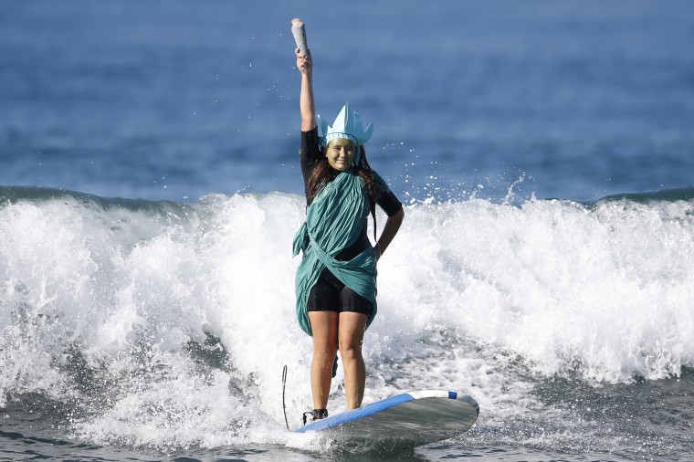 Colby Palacio, 14, rides a wave dressed as the Statue of Liberty during the 7th annual ZJ Boarding House Haunted Heats Halloween surf contest in Santa Monica, California. (Lucy Nicholson/Reuters)
