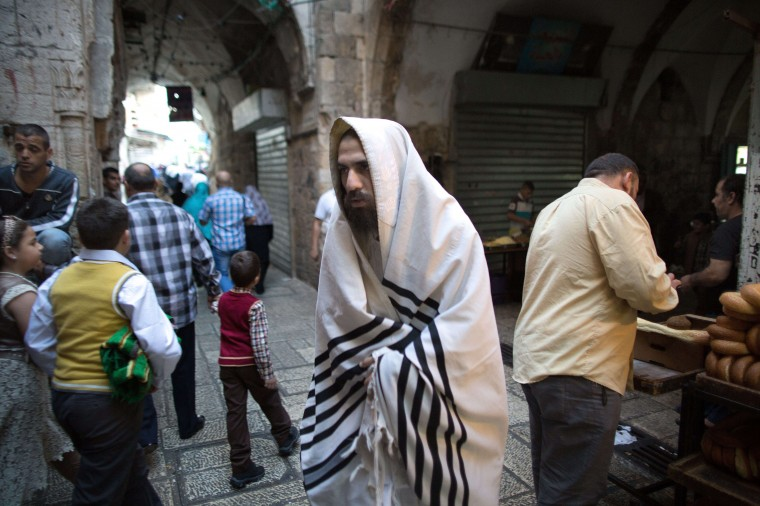 An Ultra-orthodox Jewish man returning from Yom Kippur prayers in the Western Wall walks past Palestinian Muslims on their way to the Al-Aqsa Mosque compound for the Eid al-Adha prayers in Jerusalem's old city, where the two holy sites are located. Israel is in security lockdown for the Jewish fast of Yom Kippur, which is coinciding with the Muslim festival of Eid al-Adha for the first time in three decades. The concurrence of the holy days has not occurred for 33 years because the two faiths use different lunar calendars. (Menahem Kahana/AFP-Getty Images)