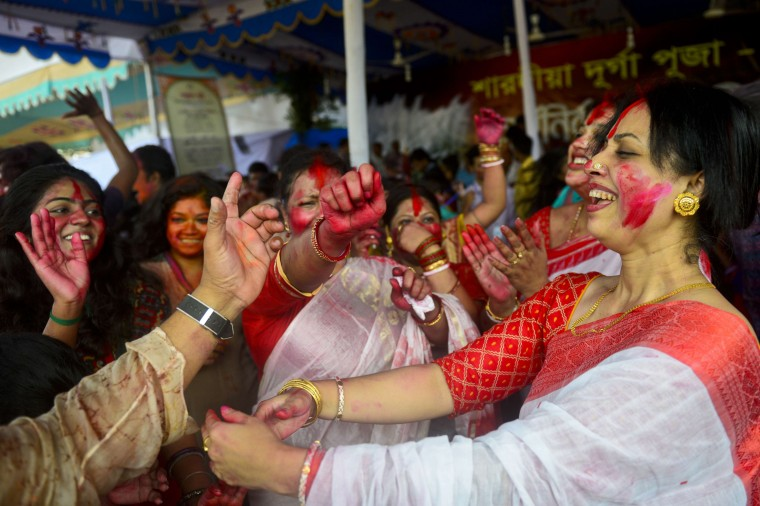 Bangladeshi Hindu devotees put vermillion and color on each other's faces as they dance on the final day of the Durga Puja Festival in Dhaka. The five-day Durga Puja festival commemorates the slaying of a demon king Mahishasur by goddess Durga, marking the triumph of good over evil. (Munir uz Zaman/AFP-Getty Images)