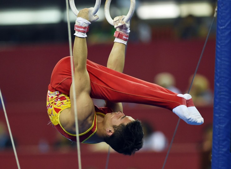 China's Deng Shudi performs on the rings during the men's all-around final at the Gymnastics World Championships in Nanning. (GREG BAKER/AFP/Getty Images)