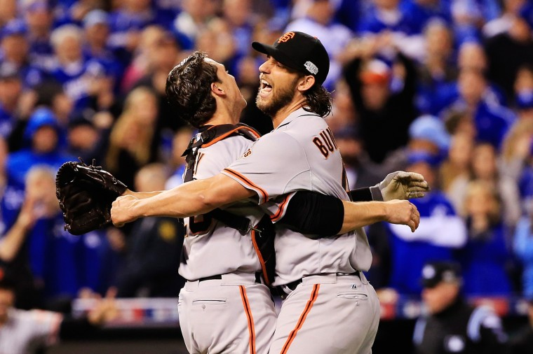 Buster Posey #28 and Madison Bumgarner #40 of the San Francisco Giants celebrate after defeating the Kansas City Royals to win Game Seven of the 2014 World Series by a score of 3-2 at Kauffman Stadium on October 29, 2014 in Kansas City, Missouri. (Photo by Jamie Squire/Getty Images)