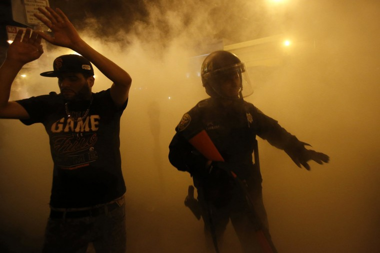 A reveller raises his arms after being ordered to disperse by the police during a street celebration in San Francisco, California October 29, 2014. The San Francisco Giants beat the Kansas City Royals 3-2 on Wednesday to win their third World Series title in five seasons. (Stephen Lam/Reuters)