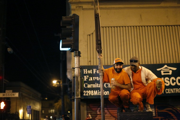 Revellers squat by a street sign in celebration in San Francisco, California October 29, 2014. The San Francisco Giants beat the Kansas City Royals 3-2 on Wednesday to win their third World Series title in five seasons. (Stephen Lam/Reuters)