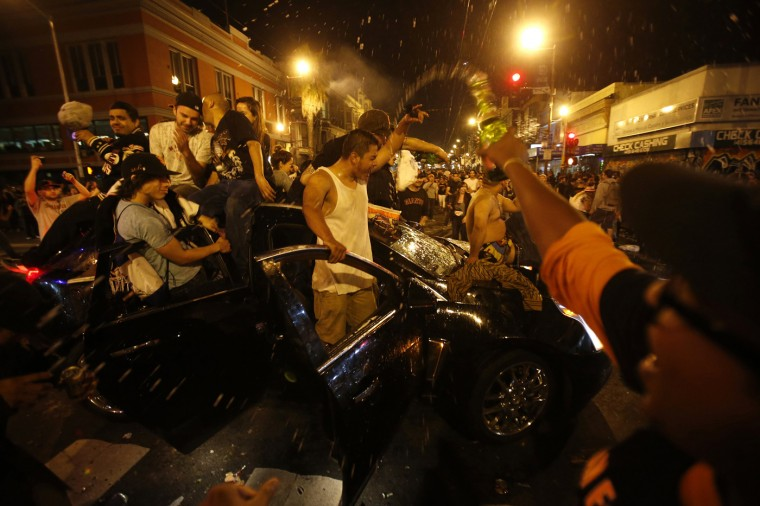 Revellers celebrate from a moving vehicle in San Francisco, California October 29, 2014. The San Francisco Giants beat the Kansas City Royals 3-2 on Wednesday to win their third World Series title in five seasons. (Stephen Lam/Reuters)