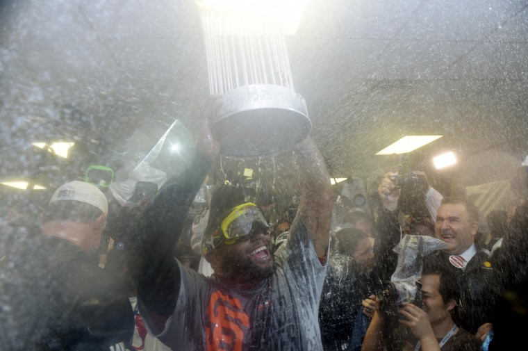 San Francisco Giants third baseman Pablo Sandoval celebrates with the Commissioners Trophy in the clubhouse after game seven of the 2014 World Series against the Kansas City Royals at Kauffman Stadium. (Christopher Hanewinckel/USA TODAY Sports)
