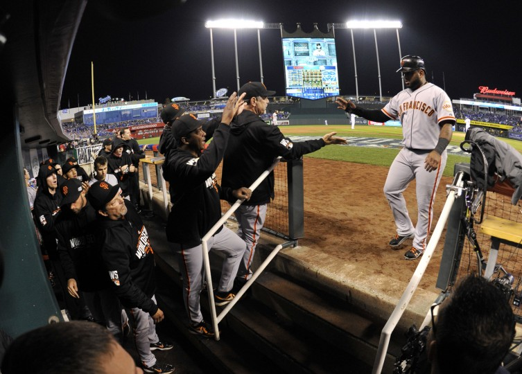 San Francisco Giants third baseman Pablo Sandoval (right) is welcomed back to the dugout after scoring a run against the Kansas City Royals in the second inning during game seven of the 2014 World Series at Kauffman Stadium. (Christopher Hanewinckel-USA TODAY Sports)