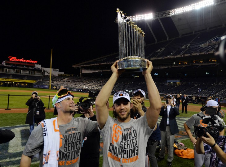 San Francisco Giants starting pitcher Ryan Vogelsong (left) watches as teammate Madison Bumgarner (middle) hoists the Commissioners Trophy after game seven of the 2014 World Series against the Kansas City Royals at Kauffman Stadium. (Peter G. Aiken-USA TODAY Sports)