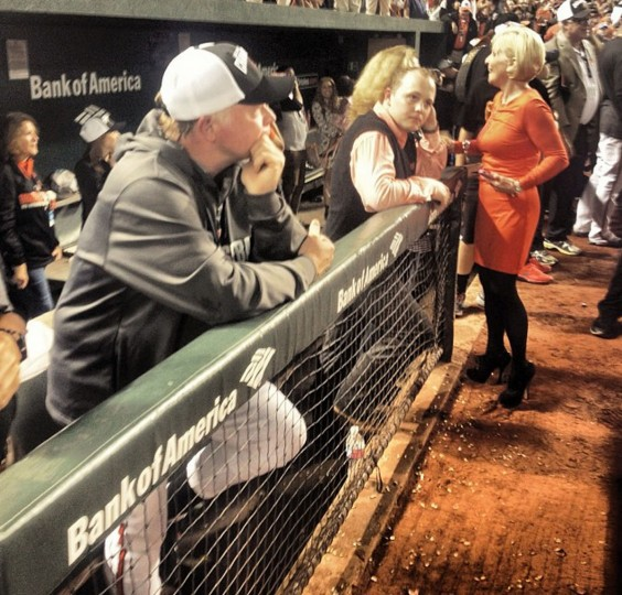 Orioles manager Buck Showalter stands on the front step of the dugout on Sept. 17, 2014, quietly watching his team celebrate their AL East championship, the O's first division title since 1997. Showalter's son, Nathan, and wife, Angela, are to his left.