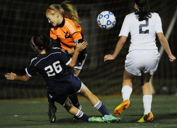 Perry Hall's Bailey D'amico, left, crashes into Catonsville goalie Natalie Croom, center, during a sectional final soccer game at Catonsville High School on Thursday, Oct. 30, 2014. (Jon Sham/BSMG)